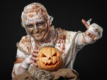 The mummy is thumbup in the studio and smiling. The mummy is thumbup in the studio and holding the  pumpkin Stock Image