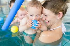 Mums and babies having fun at infant swimming course Royalty Free Stock Photo