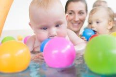 Mums i dzieci ma zabawę przy dziecięcym pływackim kursem Zdjęcie Royalty Free