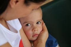 Mums little boy. Cute little boy looking intently, with mother lovingly holding him Stock Photography