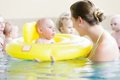 Mothers and kids having fun together playing with toys in pool royalty free stock photo