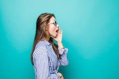 Mun för attraktivt nätt rop för flicka t för sidosikt öppna och rymmahänder nära kanter, medan stå på blå bakgrund royaltyfri foto
