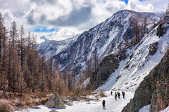 MUNCH-SARDYK, BURYATIA, RUSSIA - April 30.2016: Group of climbers goes on channel frozen river in mountains Royalty Free Stock Photo