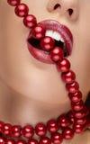 Mund mit dem roten Lippenstift, der rote Perlen beißt Stockfoto