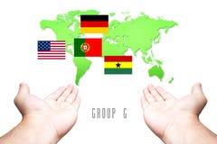 Mundial bandera de 2014 grupos-G con el fondo de la mano y del mapa del mundo fotografía de archivo libre de regalías
