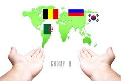 Mundial bandera de 2014 grupos-h con el fondo de la mano y del mapa del mundo fotos de archivo