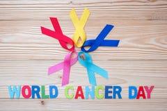 Mundo câncer dia o 4 de fevereiro fitas coloridas da conscientização; azul, vermelho, rosa e cor amarela no fundo de madeira para foto de stock royalty free