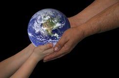Mundo da terra arrendada do homem e do menino no fundo preto Imagens de Stock Royalty Free