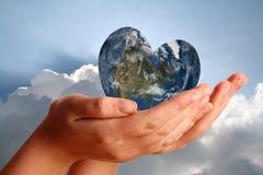 Mundo dado forma coração nas mãos novas dos womans Foto de Stock Royalty Free