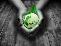 Mundo del vidrio verde en la mano del corazón imagenes de archivo