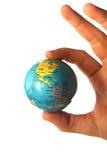 Mundo em uma mão da pessoa   Imagens de Stock Royalty Free