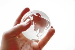 Mundo en una mano, globo de cristal que brilla intensamente Fotografía de archivo libre de regalías