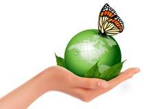 Mundo verde con la hoja y la mariposa en mano de la mujer. Fotografía de archivo libre de regalías