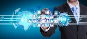 Mundos de conexão do homem de negócios aos ícones e ao software de aplicações Imagem de Stock Royalty Free