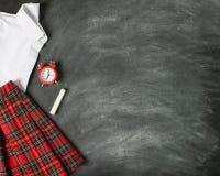 Mundurek szkolny koszula spódnicy szkockiej kraty biały budzik tło kredowa deska Pojęcie z powrotem szkoła i edukacja fotografia royalty free