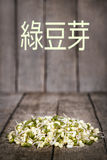 Mung bean sprouts. In front of a wooden rustic background with copyspace. Chinese characters which meaning Stock Photos