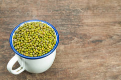 Mung beans in vintage zinc cup. Mung beans in white cup on a wooden table Stock Images