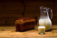 Munga da una brocca di vetro versata in un vetro, una pagnotta del pane di segale, orecchie Immagini Stock