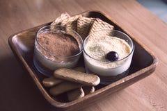 Munga la torta di formaggio, decorata con le ciliege, in vetri con i biscotti in una ciotola di legno su una tavola di legno su u Fotografie Stock Libere da Diritti