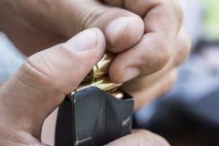 Munição da carga 9mm no fim do grampo da pistola acima Mãos, balas, compartimento e revólver Fotos de Stock