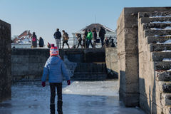 MUNICH – JANUARY 28: Girl walking on ice on frozen lake. With tourists in the background Royalty Free Stock Images