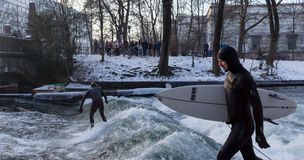 MUNICH – JANUARY 28: A surfer riding top of a wave on river Isar. Munich, Germany. People surfing on -10 degrees while everything around them is frozen Stock Image