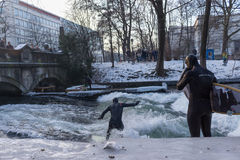 MUNICH – JANUARY 28: A surfer riding top of a wave on river Isar. Munich, Germany. People surfing on -10 degrees while everything around them is frozen Stock Photo