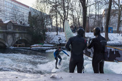 MUNICH – JANUARY 28: A surfer riding top of a wave on river Isar. Munich, Germany. People surfing on -10 degrees while everything around them is frozen Royalty Free Stock Image