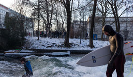 MUNICH – JANUARY 28: A surfer riding top of a wave on river Isar. Munich, Germany. People surfing on -10 degrees while everything around them is frozen Royalty Free Stock Photo