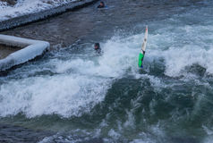 MUNICH – JANUARY 28: A surfer riding top of a wave on river Isar. Munich, Germany. People surfing on -10 degrees while everything around them is frozen Stock Photography