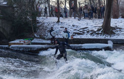 MUNICH – JANUARY 28: A surfer riding top of a wave on river Isar. Munich, Germany. People surfing on -10 degrees while everything around them is frozen Stock Photos
