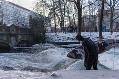 MUNICH – JANUARY 28: A surfer riding top of a wave on river Isar. Munich, Germany. People surfing on -10 degrees while everything around them is frozen Royalty Free Stock Photos