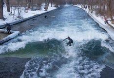 """MUNICH †""""JANUARI 28: En surfareridningöverkant av en våg på floden Isar Arkivfoto"""