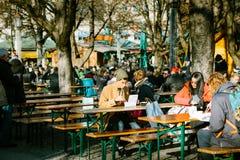 Munich, Alemanha, o 29 de dezembro de 2016: Um homem novo come no café da rua com fast food e alimento nacional perto da central Imagem de Stock Royalty Free
