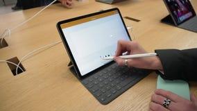 Munich, Alemania - 20 de noviembre de 2018: Mujer que usa la favorables tableta del nuevo iPad y lápiz de Apple en Apple Store almacen de video