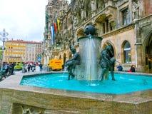 Munich, Allemagne - 1er mai 2017 : Les gens s'asseyant au bord de la fontaine de poissons avec la ville nouvelle Hall à l'arrière Image libre de droits
