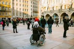 Munich, Allemagne, le 29 décembre 2016 : Une femme agée dans un fauteuil roulant examine les vues de Munich sur la place principa Photo libre de droits