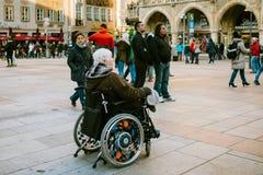 Munich, Allemagne, le 29 décembre 2016 : Une femme agée dans un fauteuil roulant examine les vues de Munich sur la place principa Image stock