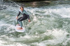 MUNICH - AUGUST 08: An unidentified female surfer works the wave at the Surf & Style  August 08, 2015 in Munich Royalty Free Stock Photo