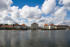 Munich Castle. Baroque castle in Munich, Germany, with many swans swimming in the beautiful lake in front of the main facade royalty free stock photos