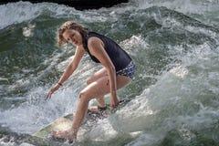 MUNICH - 8 DE AGOSTO: Um surfista fêmea não identificado trabalha a onda na ressaca & no estilo 8 de agosto de 2015 em Munich Foto de Stock