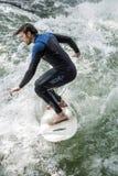 MUNICH - 8 DE AGOSTO: Una persona que practica surf de sexo masculino no identificada trabaja la onda en Eisbach Foto de archivo libre de regalías