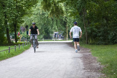 Munich Englischer Park, Germany-July 08: Unidentified people as. Runner and cyclist doing work out in the park on July 08.2011 in Munich, Germany as editorial Stock Photos