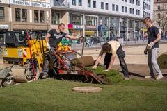Munich, Germany - April 13, 2013: Mechanized laying a new lawn. Stock Photo