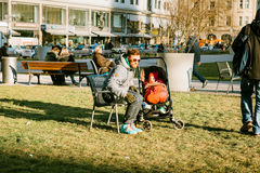 Munich, Germany, December 29, 2016: The father walks with a small child in a stroller in a park in the center of Munich. Care, outdoor recreation, childhood Stock Photos