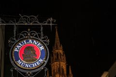 Paulaner Beer logo in front of Munich New Town Hall Neues Rathaus at night. MUNICH, GERMANY - DECEMBER 17, 2017: Paulaner Beer logo in front of Munich New Town Royalty Free Stock Images