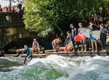 Surfer on the Eisbach in the English Garden with many spectactors stock photos