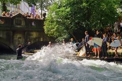 Surfer on the Eisbach in the English Garden with many spectators. This river flows through the Englischer Garden and is royalty free stock images