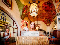 Young attractive waitress sells giants pretzels at the iconic Hofbrauhaus beer hall in Munich, Germany - ultra wide. Munich, Germany - July 29, 2018: Young royalty free stock image