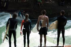 Surfers Lined Up Along the Eisbach River in Munich, Germany stock photography